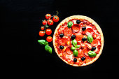 istock Meat Pizza with Ham, Pepperoni and Bacon on a black background 843276668