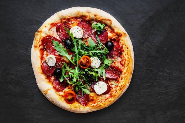 """kött pizza med smält mozzarella och tomat på svart sten bakgrund. pizza meny """". n - italy poster bildbanksfoton och bilder"""