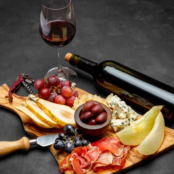Meat plate antipasti snack - Prosciutto ham, blue cheese, melon, grapes, Olives stock photo