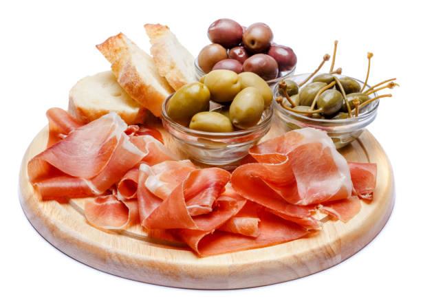 fleischplatte italienischen prosciutto crudo oder spanischen jamon auf holzbrett - brotschneidebrett stock-fotos und bilder