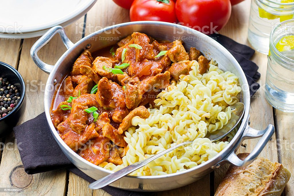 Meat pork in thick tomato gravy with pasta stock photo