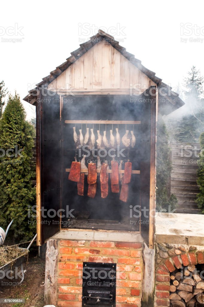 Meat prepared for smoking. Raw meat in a smokehouse. Stages of smoking royalty-free stock photo