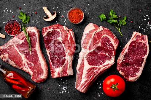 istock Meat raw steaks lie on a black background with vegetables, tomatoes, marasmade, mushrooms. background image. side view, copy space, top view 1004022680