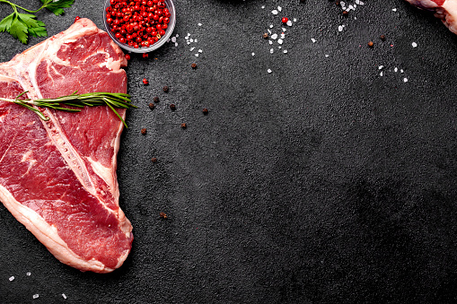 istock Meat raw steaks lie on a black background with vegetables, tomatoes, marasmade, mushrooms. background image. side view, copy space, top view 1004022704