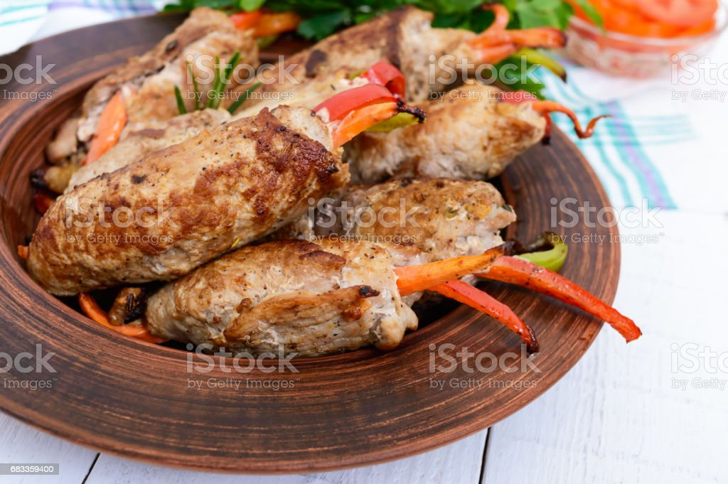 Meat rolls stuffed with sweet pepper, carrots in a clay bowl on a white wooden background. Close up stock photo