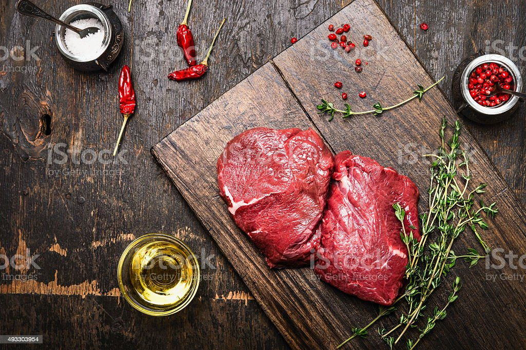 Meat steaks on rustic cutting board with thyme and spices stock photo