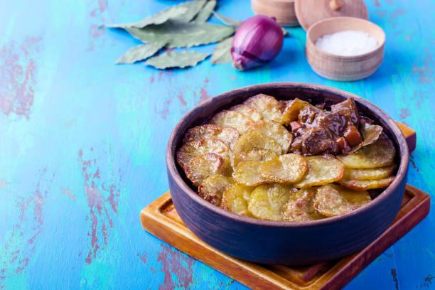 Fleisch-Eintopf, garniert mit in Scheiben geschnittenen Kartoffeln in Keramikschale, traditionelle britische Pub-Gericht – Foto