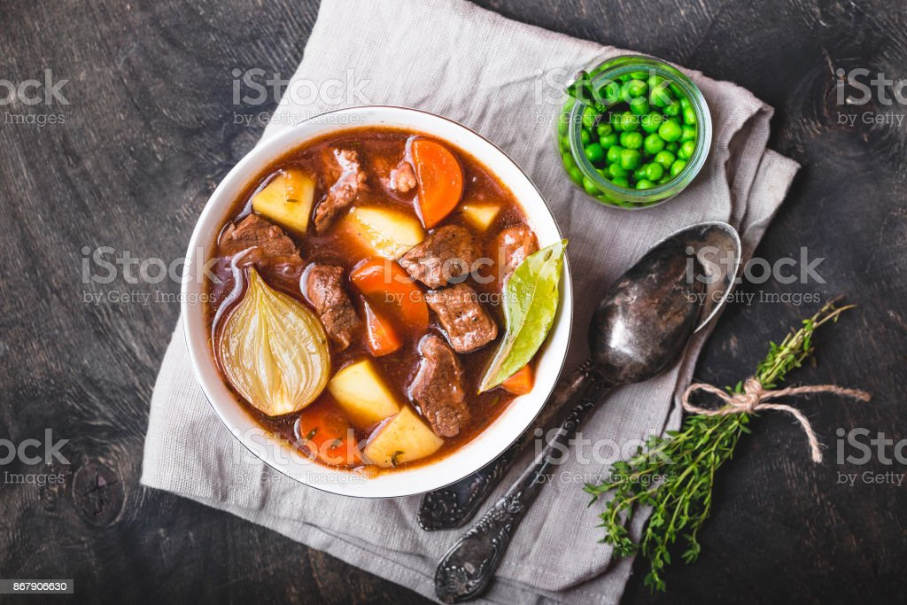 Meat stew with beef Meat stew with beef, potato, carrot, onion, spices, green peas. Slow cooked meat stew, bowl, wooden background. Hot autumn/winter dish. Closeup. Top view. Comfort food. Homemade soup/ragout/casserole Autumn Stock Photo