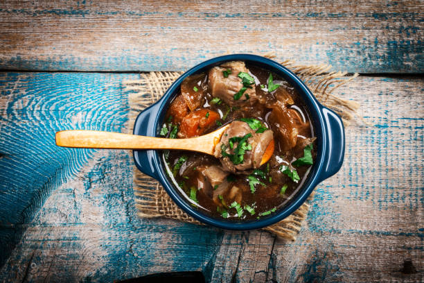 Meat stew with vegetables and herbs on old wooden table Meat stew with vegetables and herbs on old wooden table beef bourguignon stock pictures, royalty-free photos & images