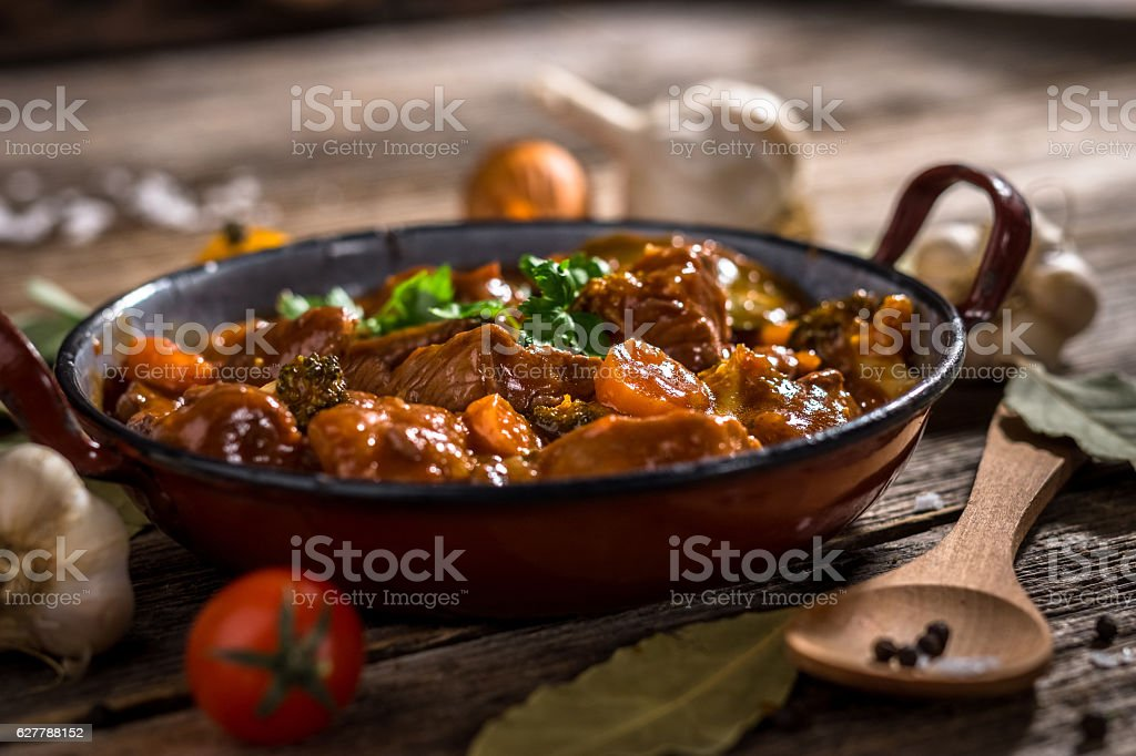 Meat stewed with vegetable on rustic wooden background stock photo