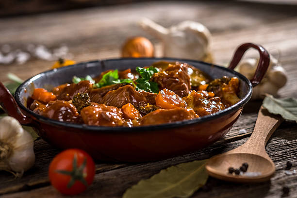 Meat stewed with vegetable on rustic wooden background Meat stewed with vegetable on rustic wooden background beef stew stock pictures, royalty-free photos & images