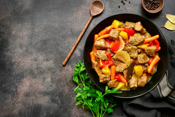 Meat stewed with vegetables Meat stewed with vegetables in a black bowl over dark slate,stone or metal background.Top view with copy space. ragout stock pictures, royalty-free photos & images