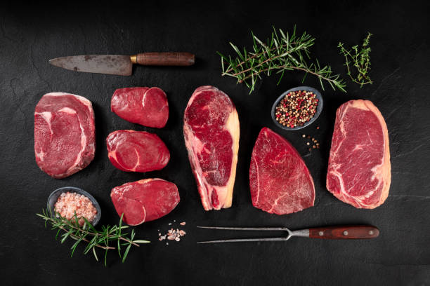 Meat, various cuts, overhead flat lay shot with a knife, a barbecue fork, salt, pepper, and rosemary stock photo
