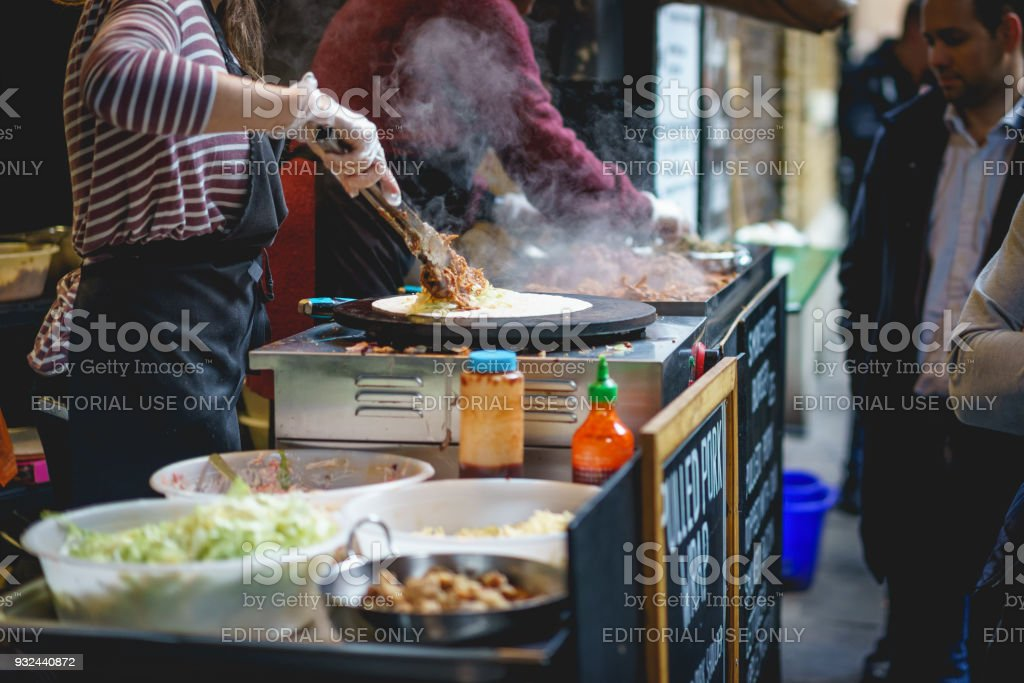 Meat wraps prepared in a stall in Borough Market in London (UK). stock photo