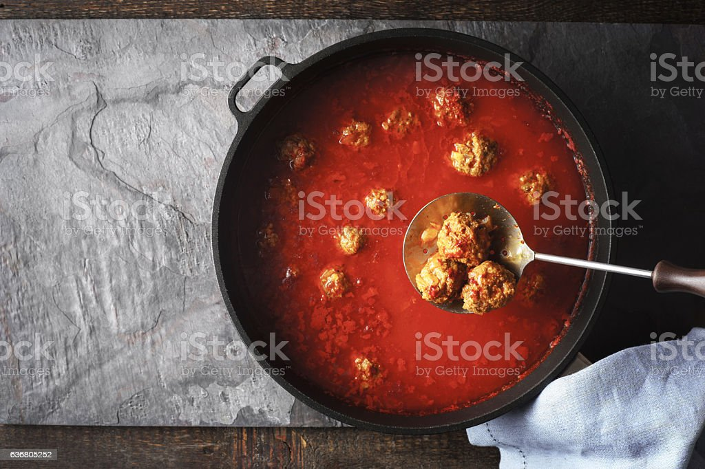 Meatball in tomato sauce  in  pan on the stone background stock photo