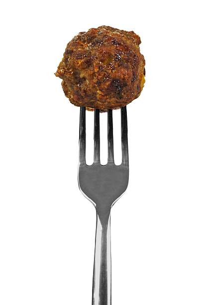 Meatball on fork over white Freshly cooked meatball on a silver fork isolated on a white background. meatball stock pictures, royalty-free photos & images