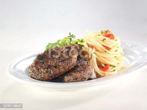 Meatball or turkish köfte with pasta and lettuce in plate.