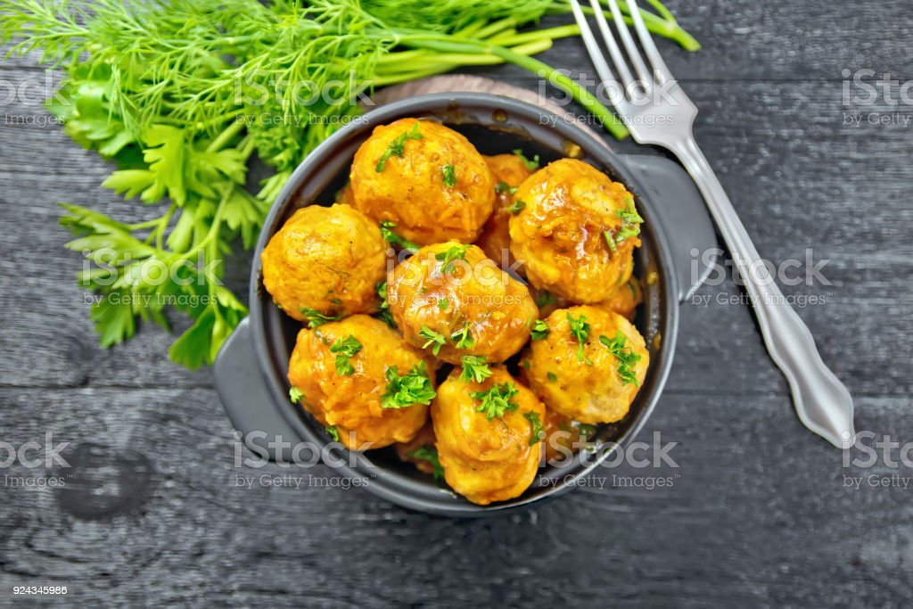 Meatballs in brazier with greens on board top stock photo