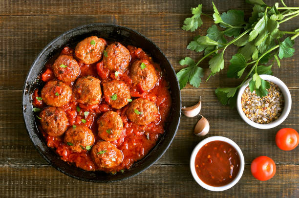 Meatballs in cast iron pan, fresh parsley and tomatoes Meatballs in cast iron pan, fresh parsley and tomatoes on wooden table, top view meatball stock pictures, royalty-free photos & images
