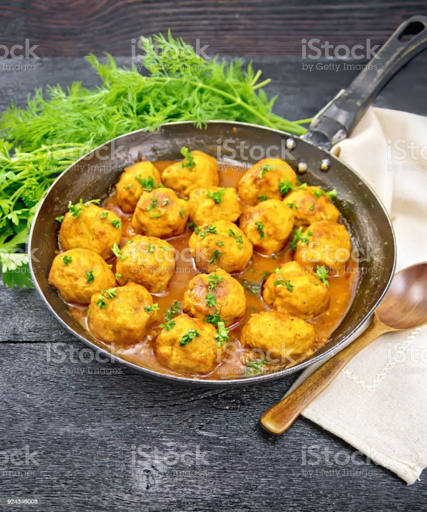Meatballs in pan with sauce on black board stock photo