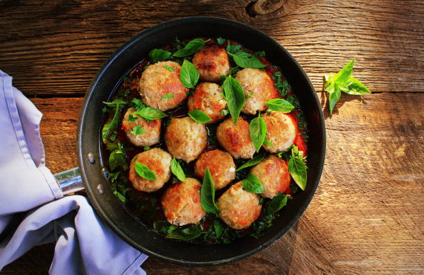 Meatballs in sweet and sour tomato sauce on rustic table. Top view stock photo
