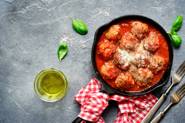 Meatballs in tomato sauce in a skillet pan Meatballs in tomato sauce in a skillet pan over dark grey slate,stone or condrete background.Top view. meatball stock pictures, royalty-free photos & images