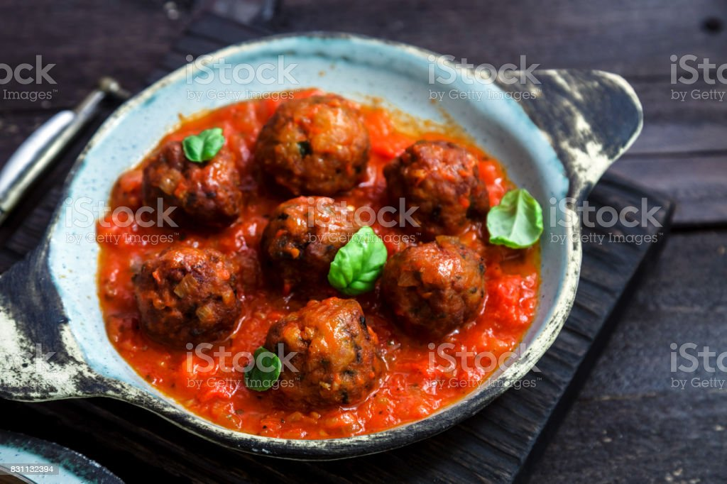 Meatballs with tomato sauce on a ceramic pan. Close view, rustic style stock photo