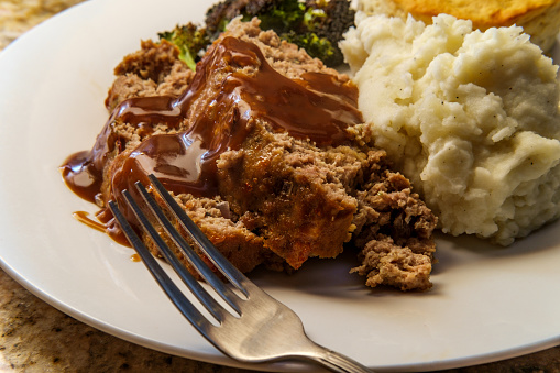 Meatloaf with gravy mashed potatoes biscuit and charred broccoli