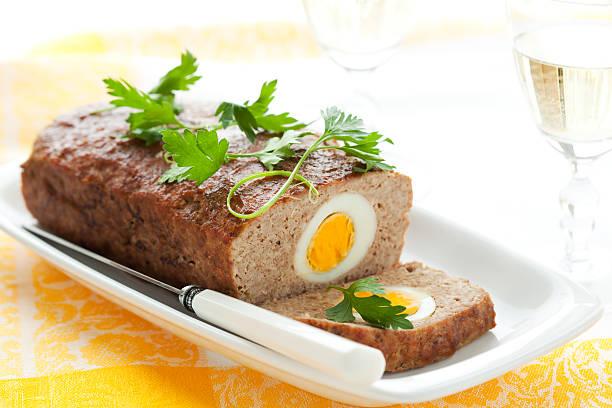 hackbraten mit gekochten eiern - hackfleischbraten stock-fotos und bilder