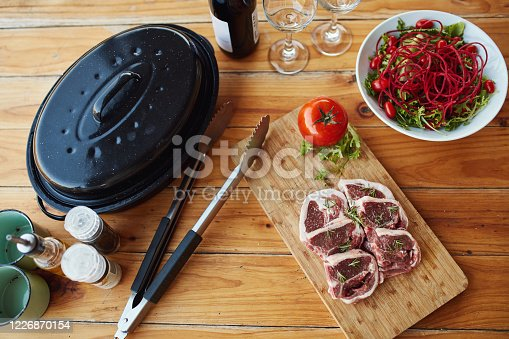 Shot of red meat and other cooking items on a chopping board at a barbecue