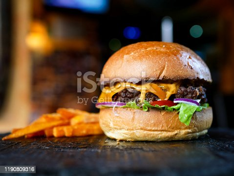 Meaty hamburger and fries on a table