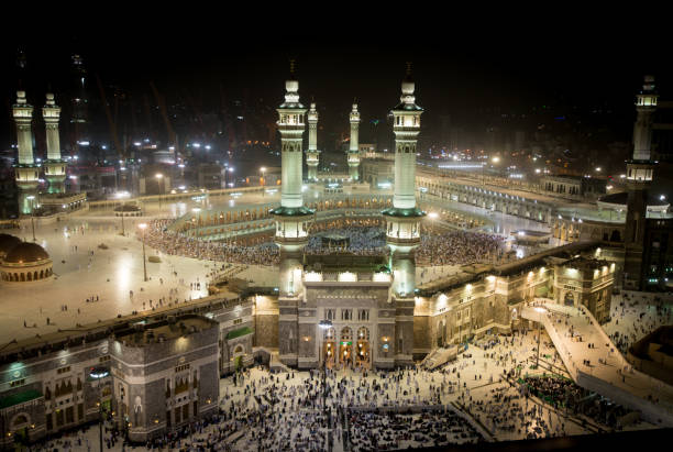 Mecca holy mosque Mecca holy mosque at night with all minarets in light with people around umrah stock pictures, royalty-free photos & images