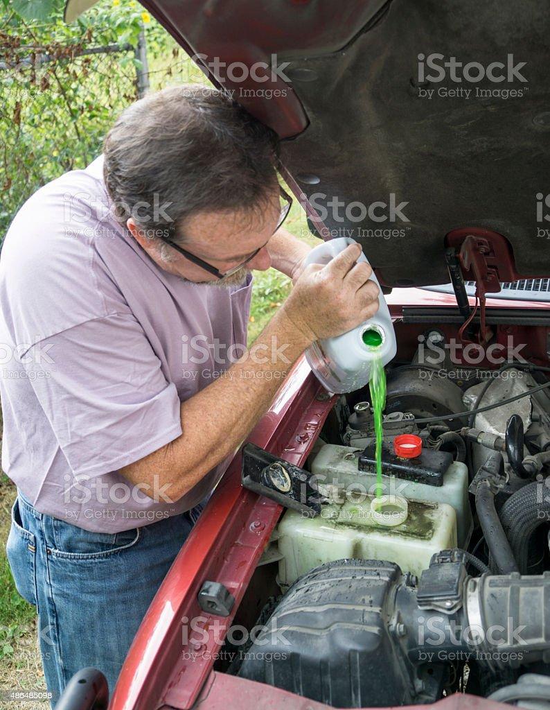 Mechanic Adding Engine Coolant To Customers Vehicle stock photo