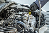 istock mechanic after change of oil in the engine checks level and quality on a probe. 1241731360