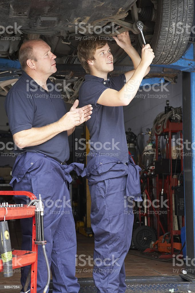 Mechanic and apprentice working on car royalty-free stock photo