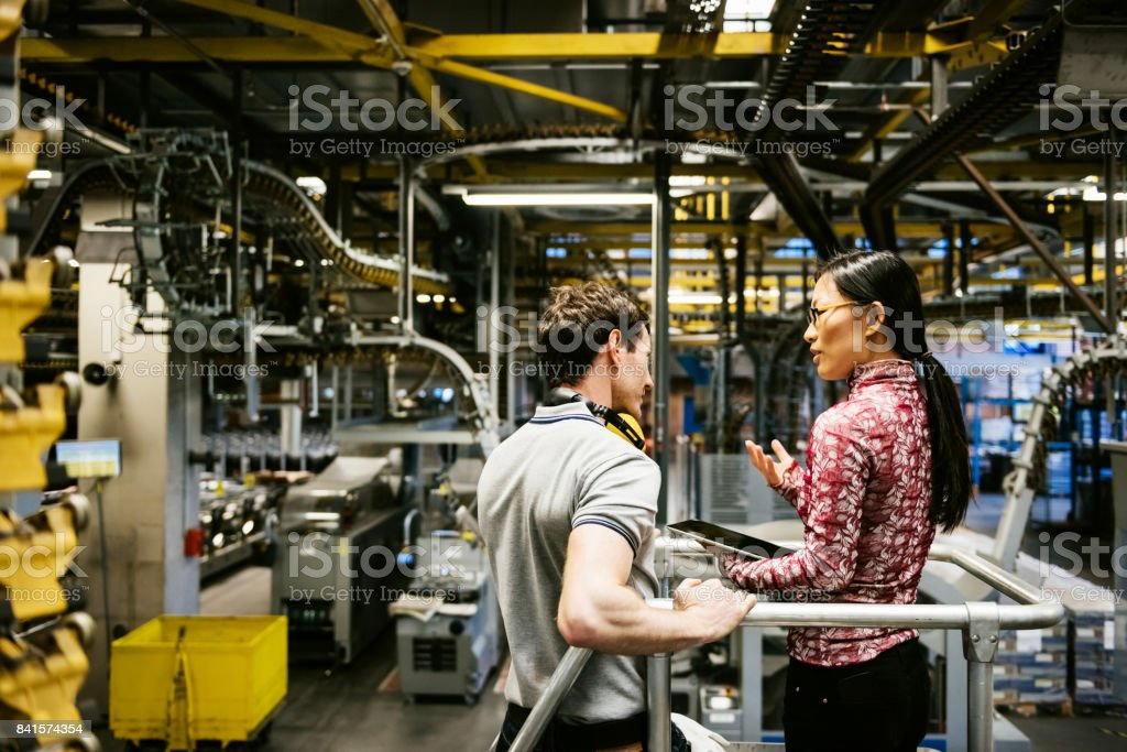 Mechanic And Female Engineer Talking in Factory stock photo