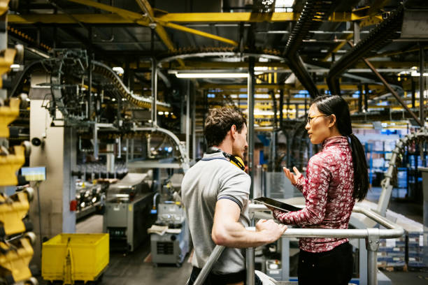 mechanic and female engineer talking in factory - factory stock photos and pictures