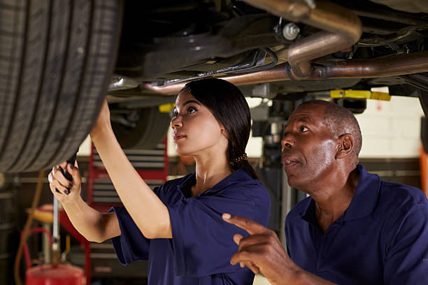 Mechanic And Female Trainee Working Underneath Car Together stock photo