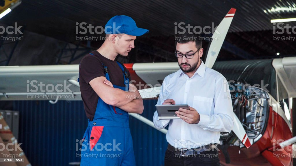 Mechanic and flight engineer having a discussion looking at a...