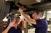 istock Mechanic And Male Trainee Working Underneath Car Together 628110734
