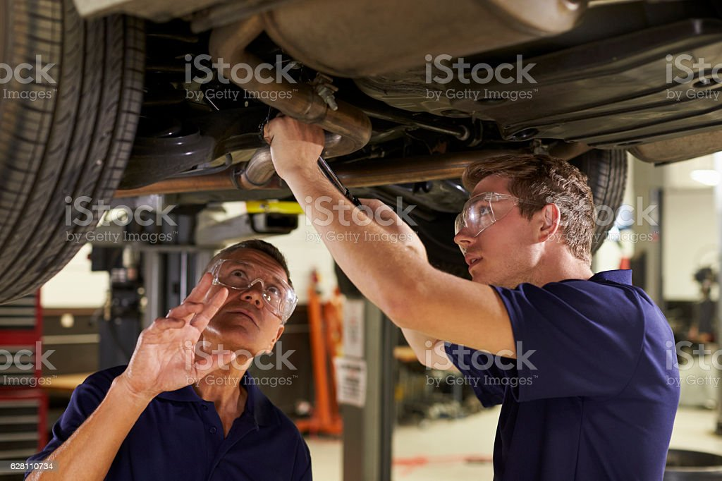 Mechanic And Male Trainee Working Underneath Car Together stock photo