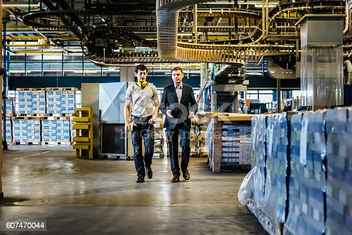 Mechanic and manager talking an walking in a big factory.