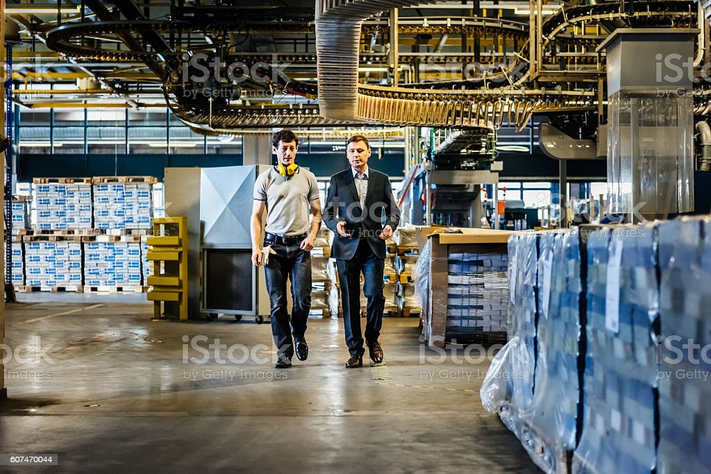 Mechanic and Manager talking and walking in factory stock photo