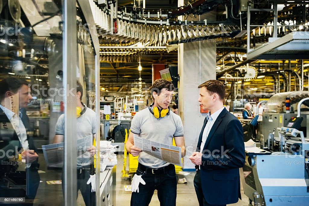 Mechanic and Manager talking in huge factory stock photo