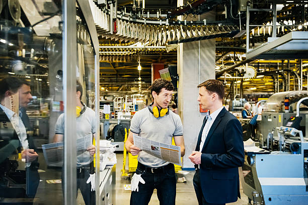 Mechanic and Manager talking in huge factory - Photo