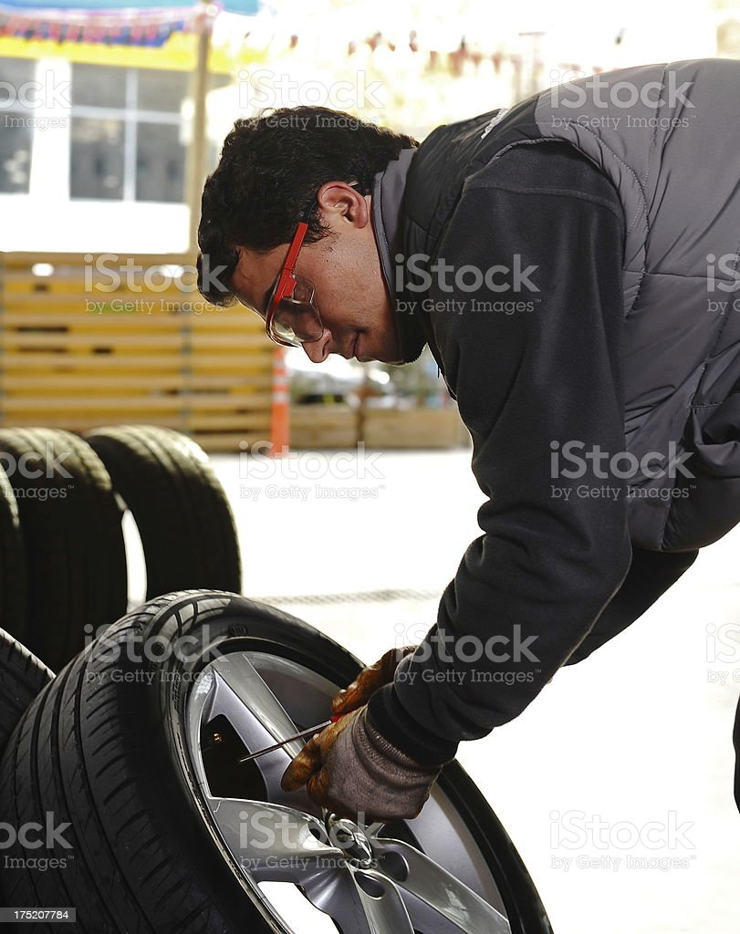 Mechanic and new tires royalty-free stock photo