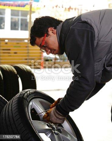 154934986 istock photo Mechanic and new tires 175207784