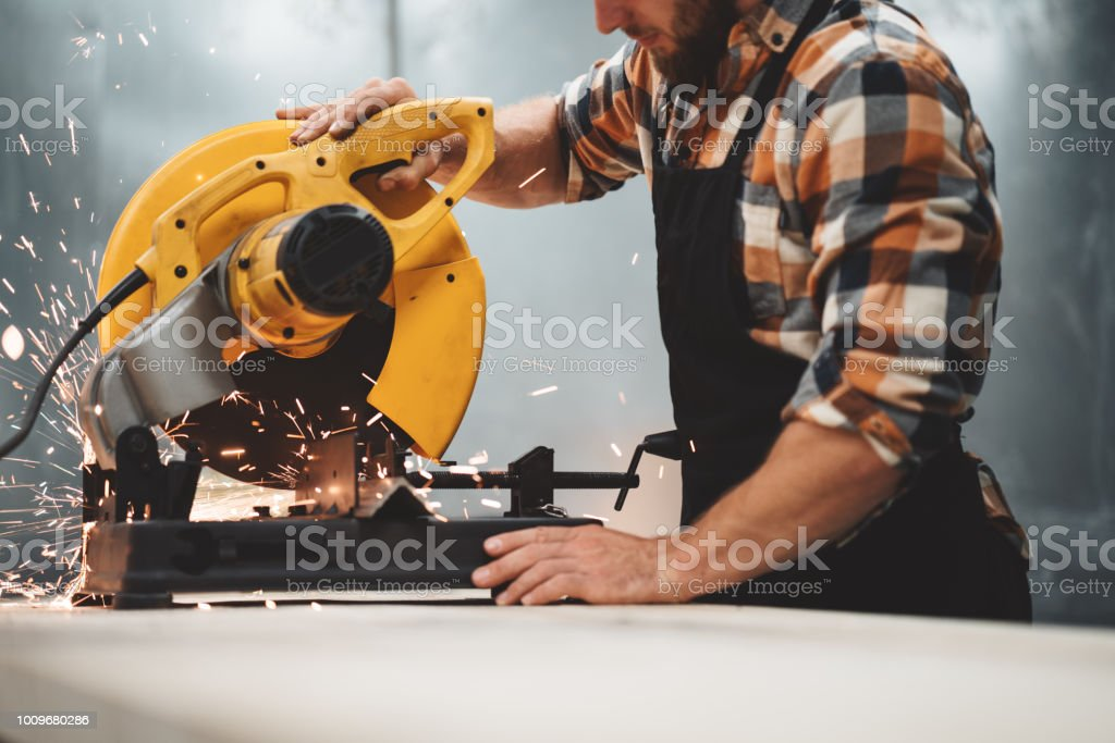 Mechanic angular grinding machine in action, sparks fly apart. Work in process on metalworking factory. Horizontal stock photo