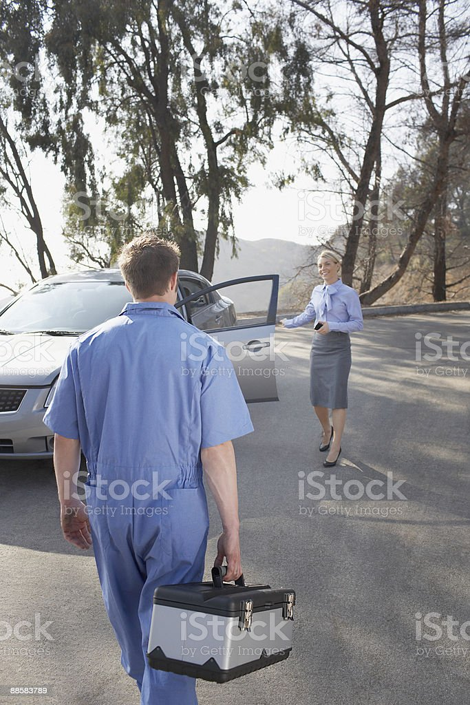 Mechanic arriving to help stranded woman royalty-free stock photo