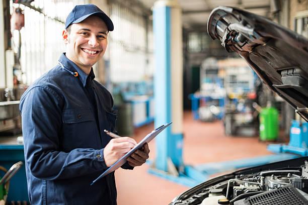mechaniker bei der arbeit in der garage - autowerkstatt stock-fotos und bilder